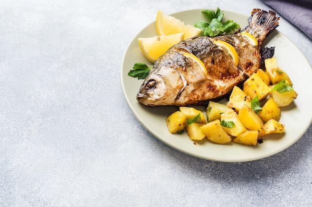 Carpa de pescados cocida al horno con verdes y patatas de limón en una placa. copia espacio