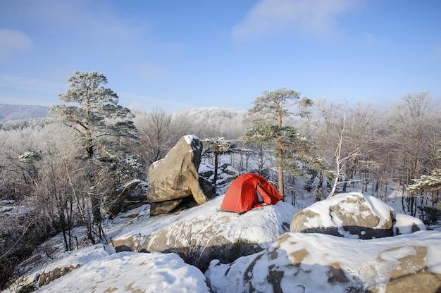 Carpa en pie de nieve en la cima de la montaña rocosa