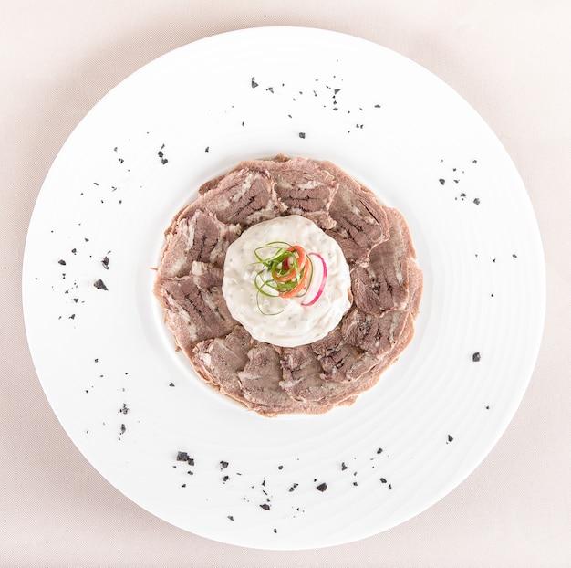 Carpaccio de buey con mayonesa, decorado con hierbas, colocado en un plato blanco