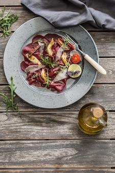 Carpaccio de ternera en plato con tomates secos alcachofas rúcula y parmesano.