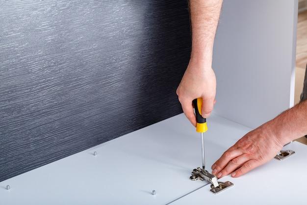 Carpenter recoge armario de muebles en blanco y negro. copie el espacio. carpintero recoge muebles con herramientas de mano destornillador. montaje de muebles. mudanzas, mejoras para el hogar, reparación y renovación de muebles.
