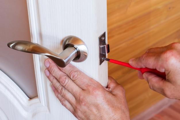 Carpenter repara la cerradura de la puerta principal. sujeta el mango con un destornillador.