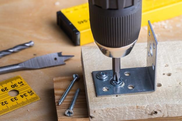 Carpenter sostiene un destornillador inalámbrico y envuelve el tornillo
