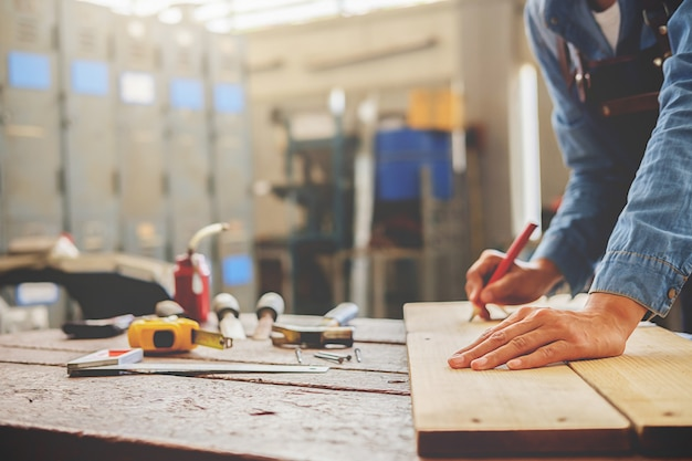 Carpenter trabajando en máquinas para trabajar la madera en carpintería.