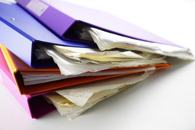 Carpeta de archivos pila de carpetas de varios colores en la mesa en la oficina.