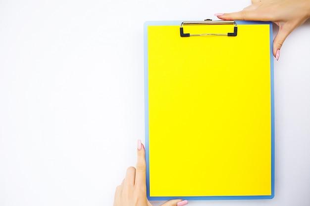 Carpeta en blanco con papel amarillo. mano que sujeta la carpeta y la manija sobre fondo blanco.