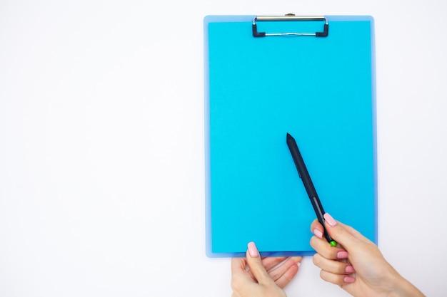 Carpeta en blanco con papel azul. de la mano que sujeta la carpeta y el bolígrafo sobre fondo blanco.