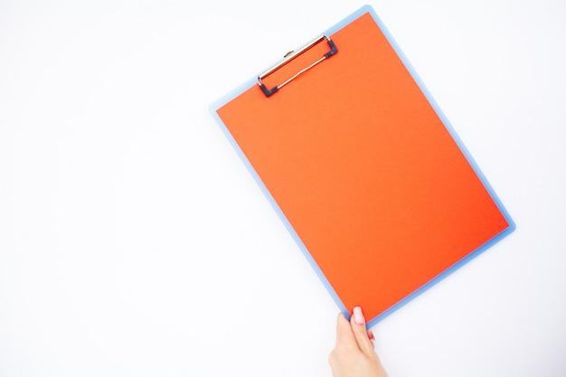Carpeta en blanco con papel rojo. de la mano que sujeta la carpeta y el bolígrafo sobre fondo blanco.