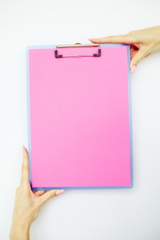Carpeta en blanco con papel rosa. mano que sujeta la carpeta y la manija sobre fondo blanco.