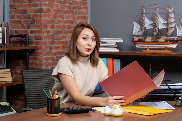 Carpeta de explotación de mujer de negocios vista frontal sentado en el escritorio