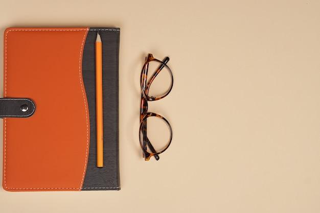 Carpeta de gafas de bloc de notas con hoja blanca oficina fondo beige papelería