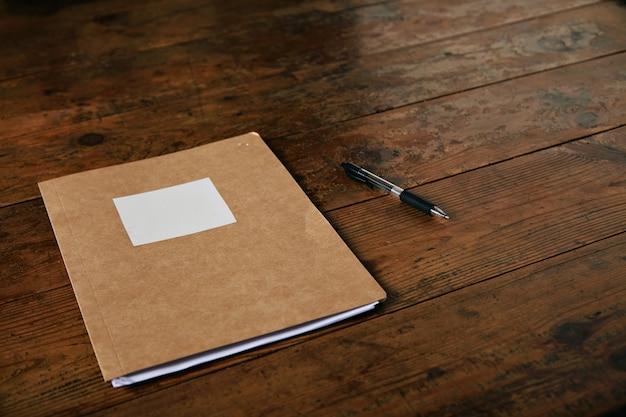 Carpeta marrón artesanal con etiqueta blanca vacía y un bolígrafo sobre una mesa rústica de color marrón oscuro