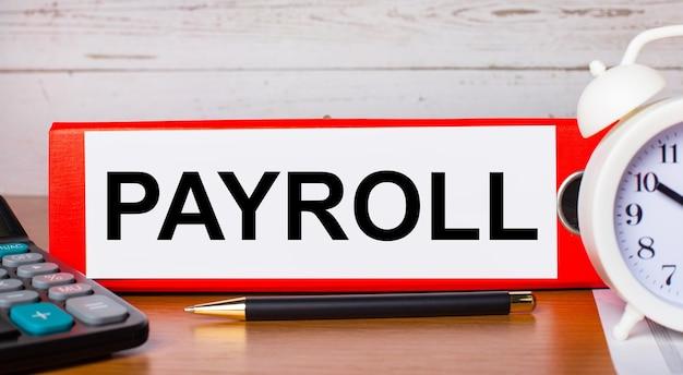 Carpeta roja para papeles con el texto payroll, despertador blanco, calculadora y bolígrafo en el escritorio. concepto de negocio