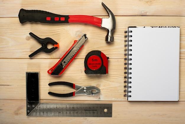 Carpintería variada, herramientas de reparación, libreta sobre madera.
