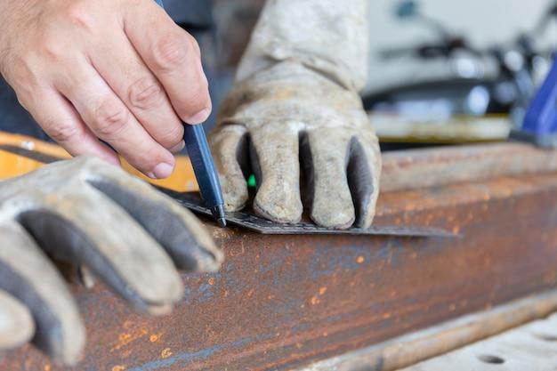 Carpintero artesano con lápiz y regla que traza la línea de corte en acero, concepto de tareas domésticas