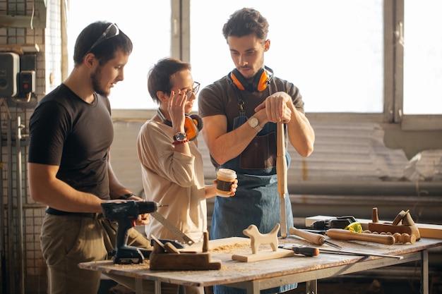 Carpintero entrenando aprendiz femenina para usar plano