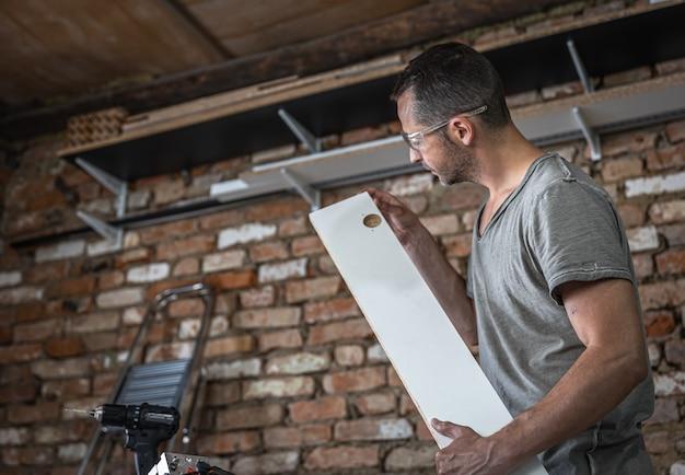 El carpintero evalúa el resultado de la perforación en el tablero.