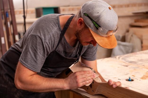 Carpintero experimentado en ropa de trabajo trabajando en taller de carpintería