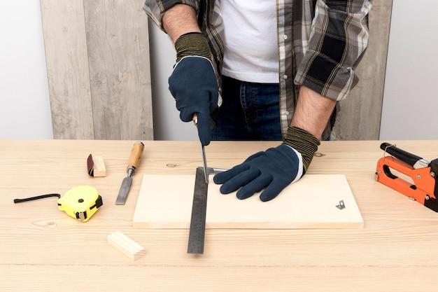 Carpintero experto con guantes de protección.