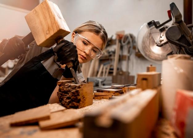 Carpintero femenino en el estudio con herramientas para esculpir madera