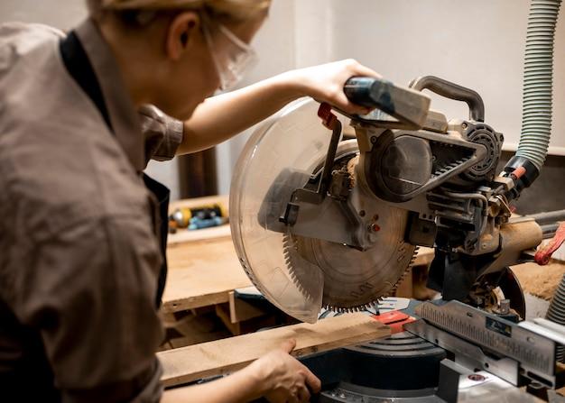 Carpintero femenino con gafas y herramienta