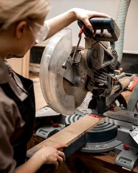 Carpintero femenino con herramienta y gafas