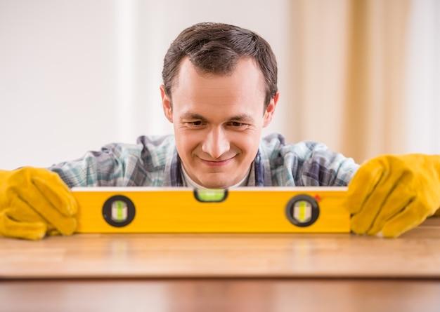Carpintero en guantes de goma que mide el tablón de madera.