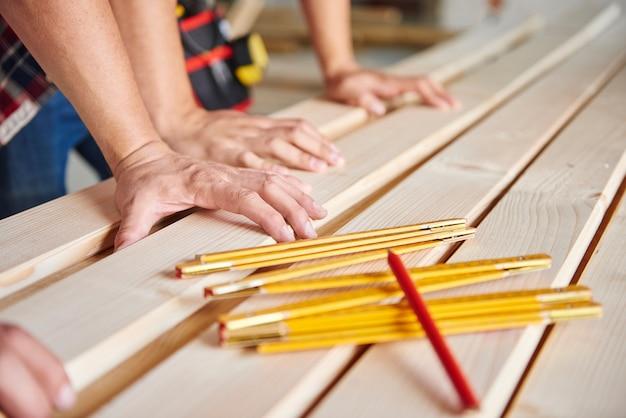 Carpintero jóvenes y mayores midiendo tablones de madera