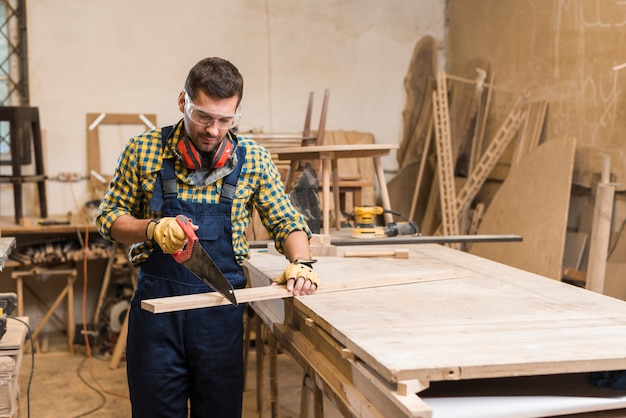 Un carpintero macho cortando la tabla con una sierra de mano en el taller.