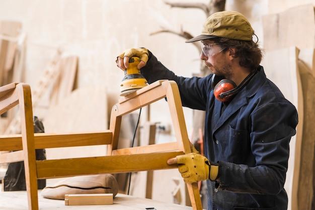 Carpintero macho lijando madera con lijadora eléctrica pulidora