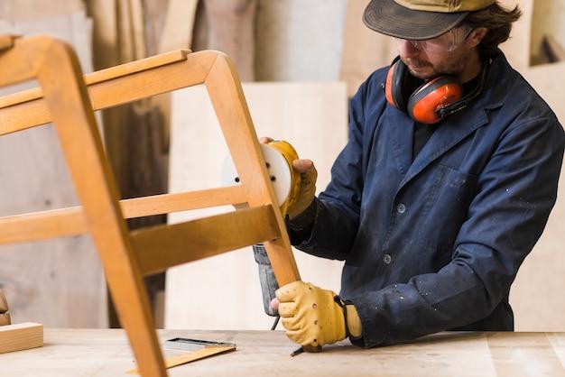 Carpintero macho lijando una madera con lijadora en mesa de trabajo