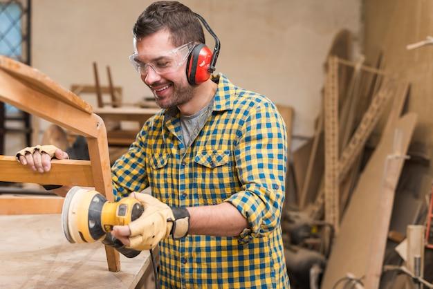Carpintero macho sonriente lijando una madera con lijadora orbital en mesa de trabajo