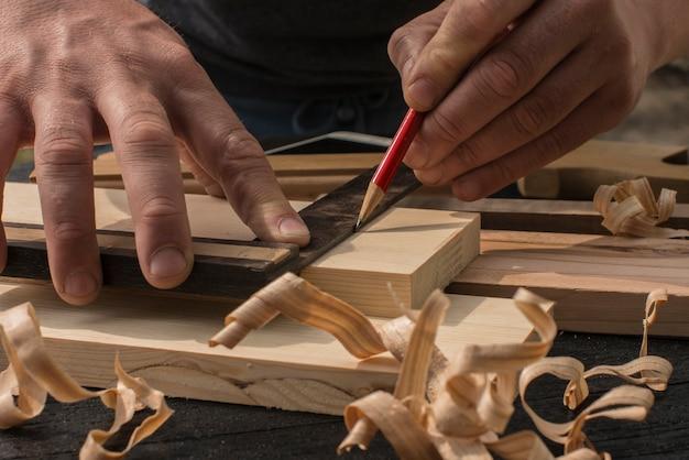 El carpintero marca con un lápiz rojo una tabla.