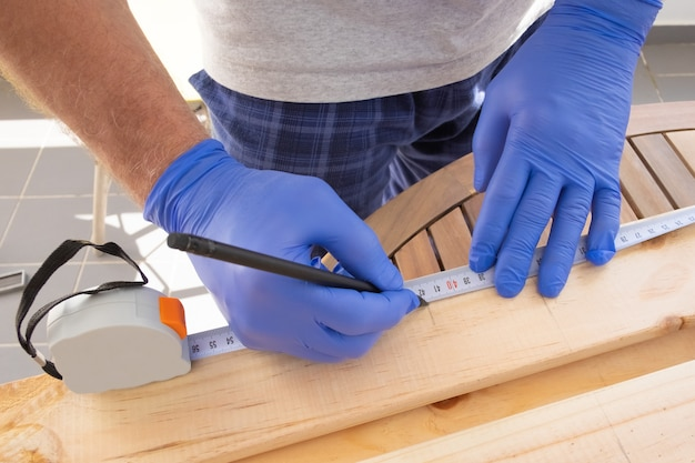Carpintero marcado escritorio de madera con cinta métrica
