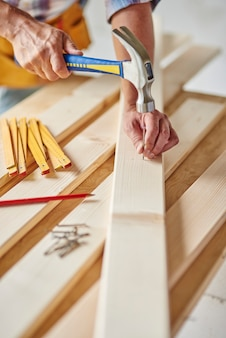 Carpintero con martillo golpea madera