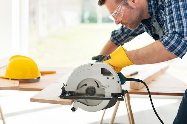 Carpintero masculino aserrado de tablas de madera