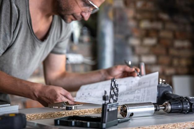 Carpintero masculino en el proceso de trabajar con madera en el taller.
