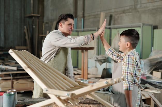 Carpintero masculino satisfecho en delantal dando cinco al hijo adolescente cuando han terminado la silla de madera en el taller