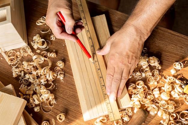 Carpintero midiendo con regla y lápiz