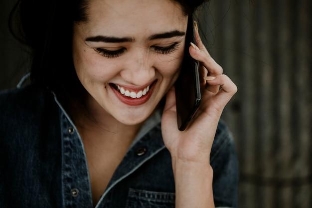 Carpintero mujer alegre hablando por un teléfono