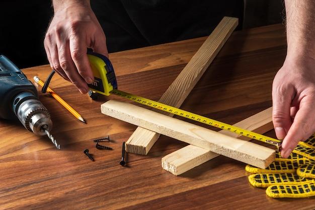El carpintero o carpintero usa una cinta de construcción para medir la longitud de un trozo de madera.