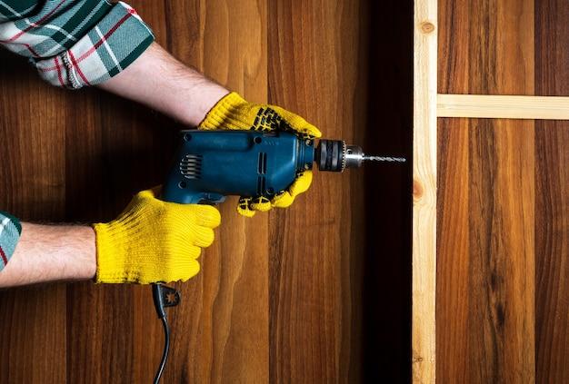 Carpintero perfora un agujero con un taladro eléctrico en una tabla de madera