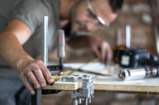 Un carpintero en el proceso, una herramienta profesional para taladrar con precisión en madera.