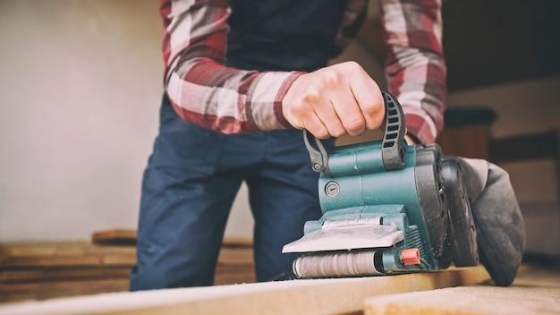 Carpintero proceso madera por lijadora de banda