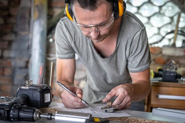 Carpintero en el proceso de trabajo, mediciones, precisión de perforación.