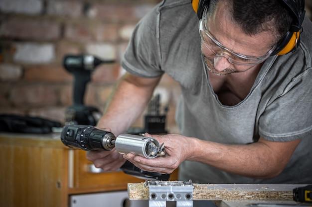 Carpintero profesional trabajando con un taladro de bisagra, trabajando con madera