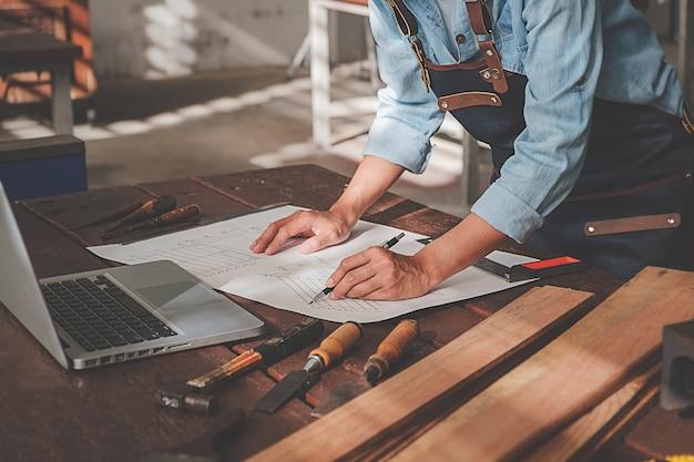 Carpintero que trabaja con el equipo en la mesa de madera en la tienda de carpintería.