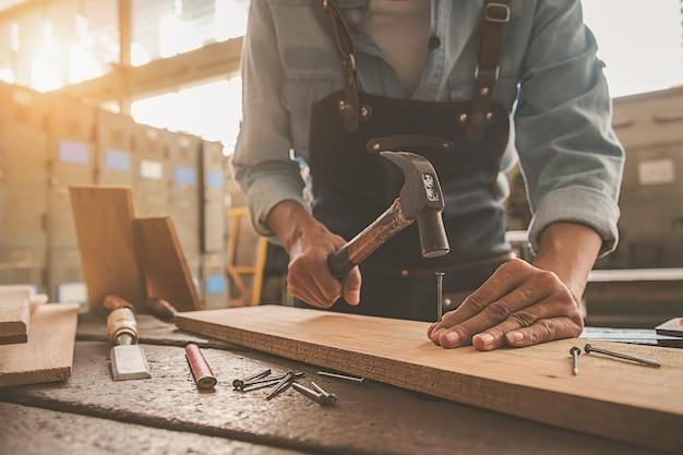 Carpintero que trabaja con el equipo en la tabla de madera en tienda de la carpintería.