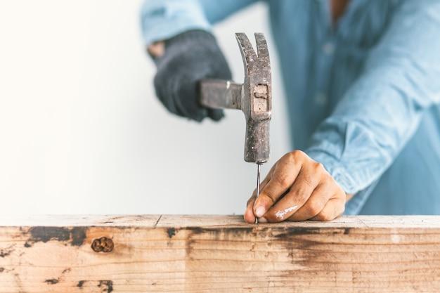 El carpintero está reparando la casa.