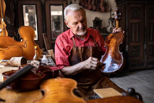Carpintero senior artesano pulido instrumento de violín en su taller de carpintero